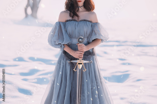 warlike girl with dark hair in long gray vintage light dress, lady of cold and frost, bare open shoulders and sharp silver sword in hands, goddess of death with red lips, character for computer games