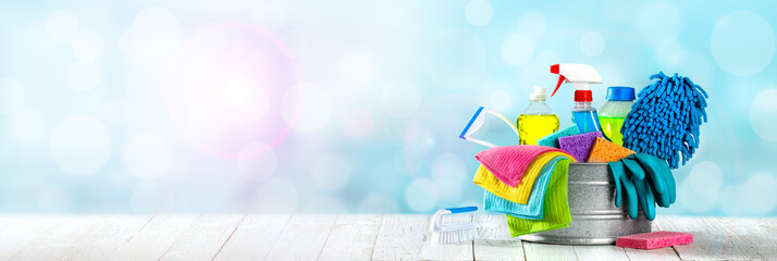 Bucket Of Cleaning Supplies On Wooden Table With Clean Blue Bubbly Background - Cleaning Services Concept