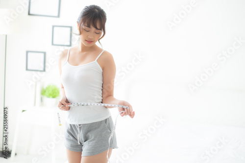 Beautiful young asian woman body diet and slim with measuring waist for weight in the bedroom, girl have cellulite and calories loss with tape measure, health and wellness concept Obraz na płótnie
