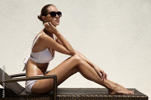 Tanned slim woman sunbathing on beach chair Fototapeta
