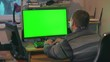A man in a shirt and pants is watching a monitor screen with a green color