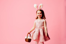Portrait Of A Smiling Little Girl With Easter Eggs Basket And Bunny Ears, On Pink