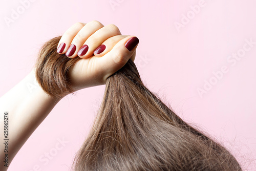 Fotografía Female hands with red manicure holding hair, pink background, hair care concept