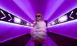 Leinwandbild Motiv Teen hipster girl standing in neon lights on street, portrait