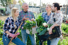 Happy Family Of Four Gardeners Holding  Harvest Of Vegetables And Greens