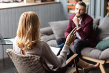 Blonde-haired Therapist Wearing Blue Ring Talking To Bearded Man