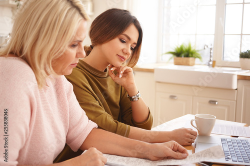 Photographie  Two Caucasian females doing finances at home together
