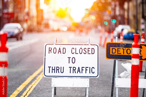 Road closed and detour sign in a road construction site work zone in the middle of a blocked street and traffic