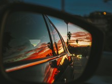 Beautiful Bright Red Sunrise / Sunset With Palm Trees And The City Of Los Angeles Is Reflected In The Side Mirror Of The Car