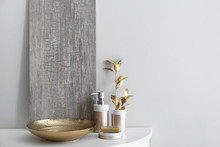 Golden Bowl With Water And Cosmetics On Table In Bathroom