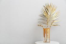 Vase With Golden Tropical Leaf On Table Against Light Background