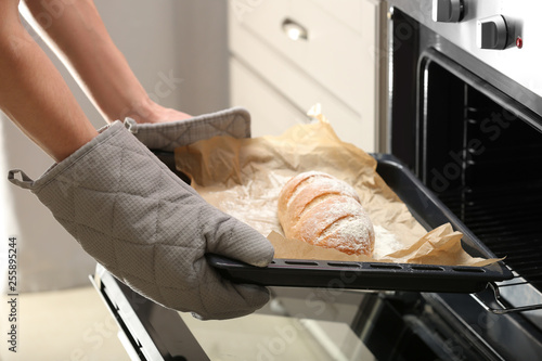 Fototapeta Taking of baking tray with homemade bread out of oven obraz