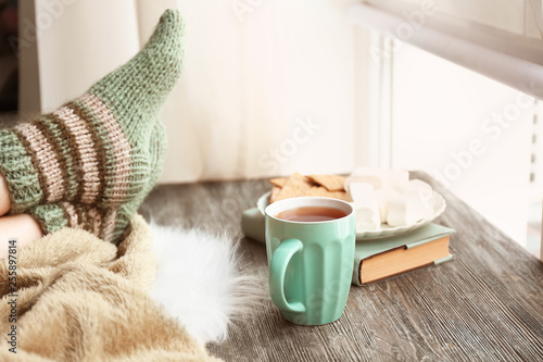 Recess Fitting Tea Cup of hot tea with legs of young woman on wooden table near window