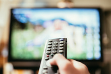 Male Hand Is Holding TV Remote...