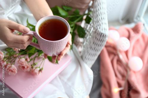 Woman drinking hot tea at home, closeup