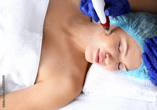 Fototapeta Young woman undergoing procedure of bb glow treatment in beauty salon obraz
