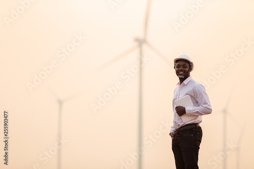 Fotografie, Obraz  African engineer wearing white hard hat standing with digital tablet against win
