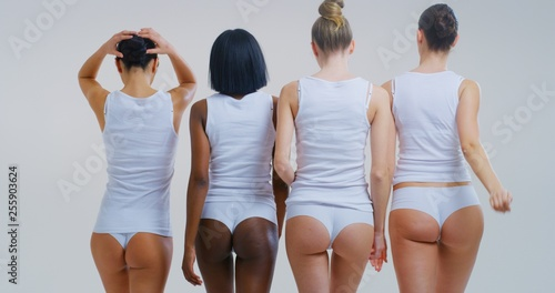 Foto op Canvas Ezel Back view of beautiful young women of different ethnicities with perfect firm and slim body in white tank shirts and panties isolated on white background.