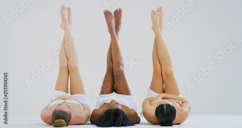 Fotografia Portrait of beautiful young women of different ethnicities with perfect firm and slim bodies with hairless soft and silky legs crossed isolated on a white background