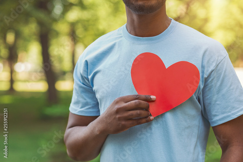 Black man holding red heart on his chest Canvas Print