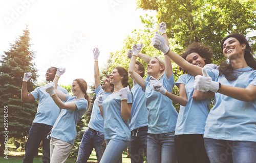 Group of happy volunteers celebrating success up in park Canvas Print