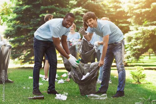 Fototapeta  Group of volunteers with garbage bags cleaning park