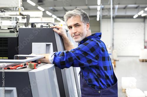 Obraz Mechanik naprawia maszynę drukarską - fototapety do salonu