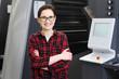 Drukarnia. Praca w drukarni. Uśmiechnięta kobieta, pracownik drukarni obsługuje maszynę drukarską.