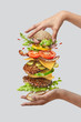 canvas print picture - Girl's hands hold big tasty homemade burger with flying natutal ingredients on a white background. Copy space.