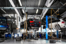 Car Repair On A Lift For The Repair Of The Chassis, Automatic Transmission And Engine In The Auto Repair Shop Or Garage. Car Workshop Concept