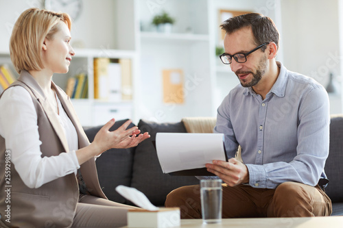 Foto Young woman explaining her problem to counselor making notes on paper during psy
