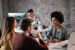 canvas print picture - Happy African American bank manager talking with her clients on a meeting.