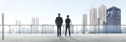 Fotografía  Rear view of two asian business people standing on modern terrace and looking at