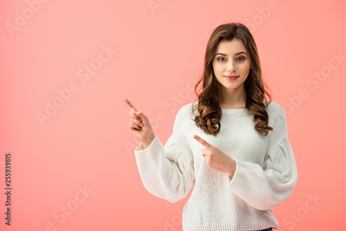 Fotografija  smiling and beautiful woman in white sweater pointing with fingers isolated on p