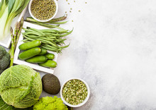 Assorted Green Toned Raw Organic Vegetables On White Stone Background. Avocado, Cabbage, Broccoli, Cauliflower And Cucumber With Trimmed Mung Beans And Split Peas In White Bowl. Space For Text