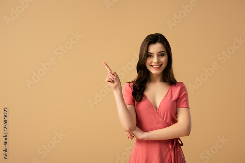 Fotografia cheerful brunette woman pointing with finger while standing isolated on brown