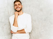 Leinwandbild Motiv Portrait of handsome smiling hipster lumbersexual businessman model wearing casual summer white clothes. Fashion stylish man posing against gray wall