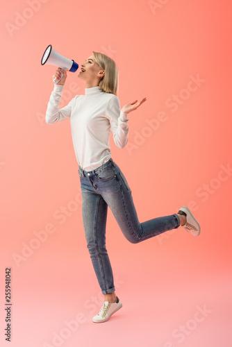 cheerful blonde woman speaking in megaphone on pink background Canvas Print