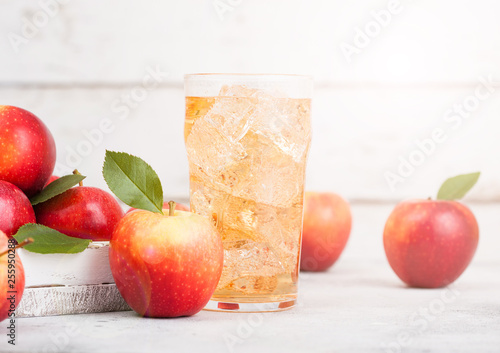 Photo Glass of homemade organic apple cider with fresh apples in box on wooden backgro