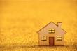 Wooden house shape on golden glitter background