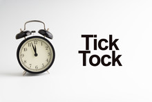 TICK TOCK Inscription Written And Alarm Clock On White Background. Business And Motivation Concept
