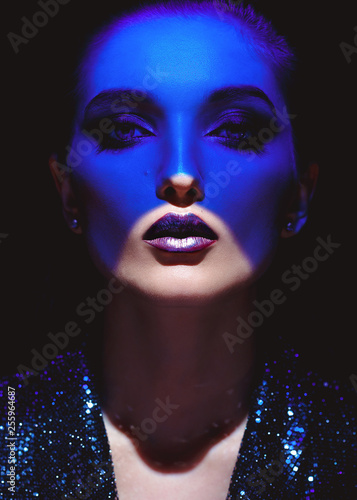 Portrait of fashion girl with stylish makeup and blue neon light on her face on the black background in the studio - 255964687