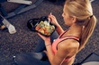 Top view of woman eating healthy food while sitting in a gym. Healthy lifestyle concept.