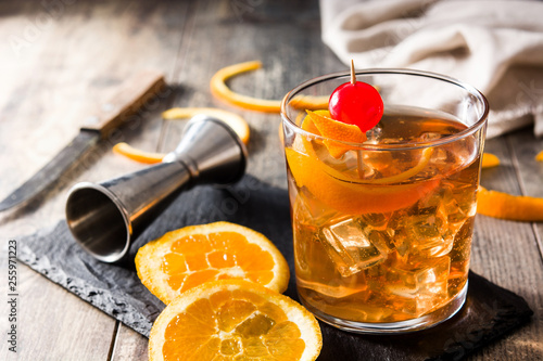 Fotografia Old fashioned cocktail with orange and cherry on wooden table
