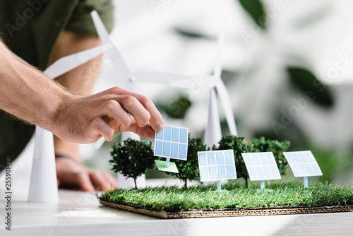 cropped view of man putting solar panels models on grass on table in office Wallpaper Mural
