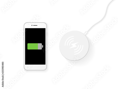 Foto wireless charging by top view of smartphone on wireless charger station on white