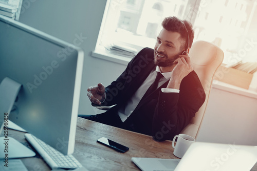 Fototapety, obrazy: Supporting clients. Top view of young man in headset talking with client and smiling while sitting in the office