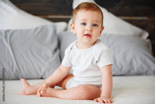 Portrait of cute baby sitting on bed Canvas Print