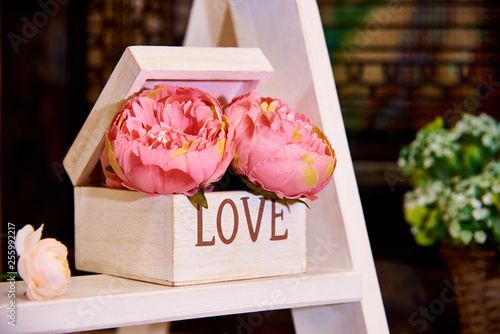Foto  Decorative flowers in wooden box on the rack.