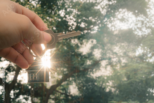 Photo House model and key in home insurance broker agent 's hand or in salesman person